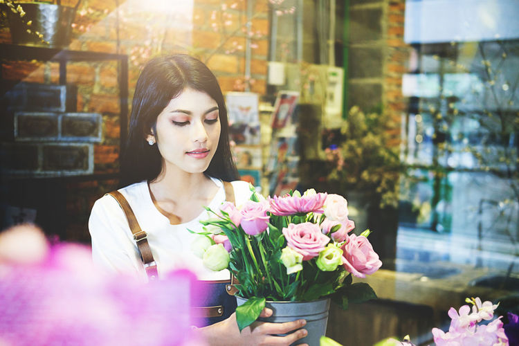 Woman adjusting flowers at shop