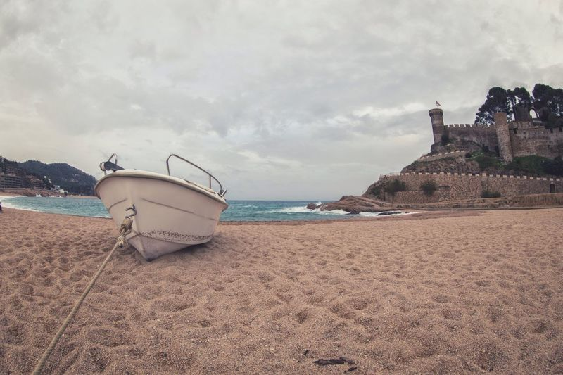 Boat moored at beach against cloudy sky