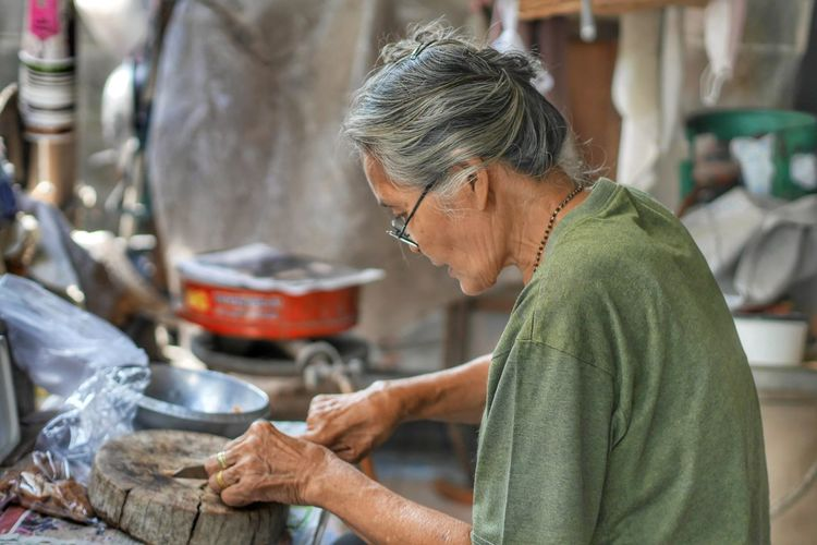 Senior Woman Cutting On Wood At Home