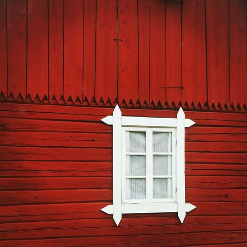 Window with white frame on red wooden wall