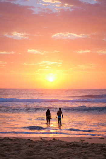 Beach sunrise Beach Beauty In Nature Cloud - Sky Horizon Over Water Lifestyles Orange Color Outdoors Reflection Sand Scenics Sea Silhouette Sky Standing Sun Sunlight Togetherness Tranquil Scene Tranquility Two People Water
