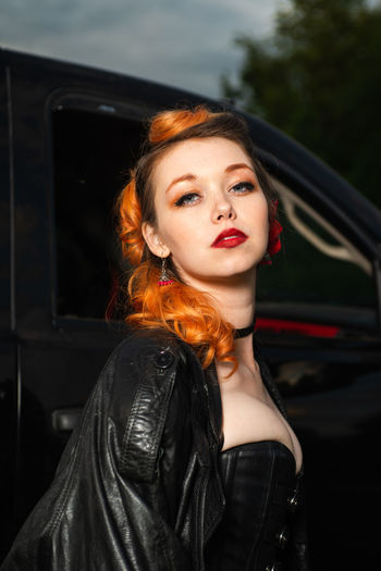 Portrait of beautiful woman with hands in car