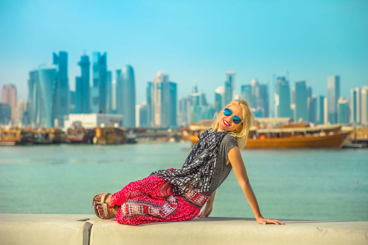 Happy caucasian woman relaxing along Corniche promenade with Dhow Harbour and Doha West Bay skyline on background. Lifestyle tourist enjoys in Doha city, Qatar, Middle East, Arabian Gulf. Doha Doha,Qatar Qatar City Town Waterfront Sea Skyline Woman Model Girl Female Tourist Seascape Tourist Attraction  The Pearl, Doha The Pearl Cityscape Holiday Vacation People Boats Dhow Architecture Building Exterior Water Built Structure Focus On Foreground Sky One Person Real People Day Nature Fashion Lifestyles Adult Women Leisure Activity Sunglasses Outdoors Office Building Exterior Skyscraper