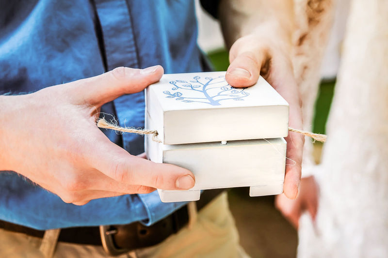 A white wooden box in the hands of a man. handmade gift packaging in rustic style