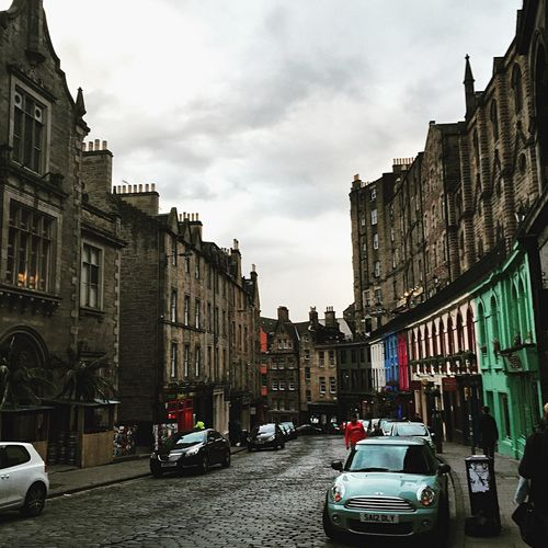 Cars on street amidst buildings in city against sky