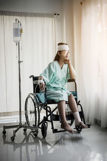 Woman With Physical Injury Sitting On Wheelchair By Iv Drip At Hospital