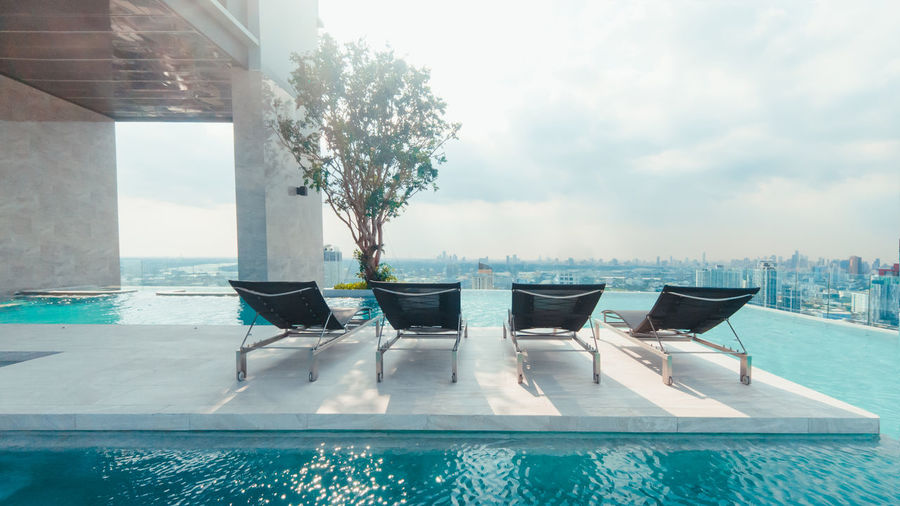 Chairs by swimming pool against sky