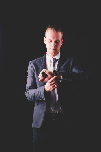 Adult Black Background Business Business Person Businessman Communication Formalwear Front View Gesturing Holding Indoors  Males  Men Mid Adult Men One Person Standing Studio Shot Three Quarter Length Well-dressed
