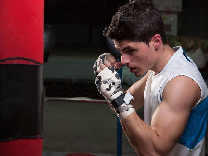 Man Punching Bag In Boxing Rink