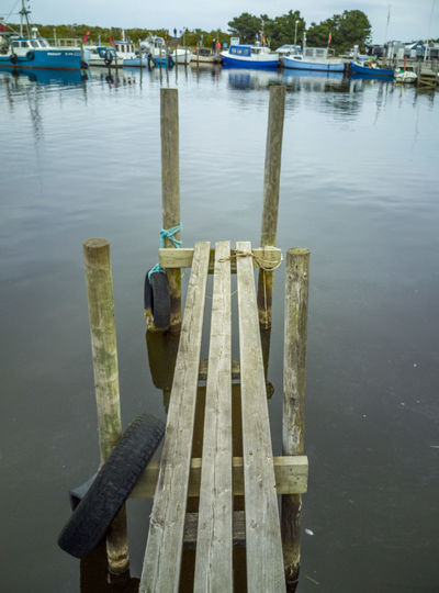 Bollard Day Harbor Lake Marina Mode Of Transportation Moored Nature Nautical Vessel No People Outdoors Pier Post Reflection Tranquility Transportation Water Wood - Material Wooden Post