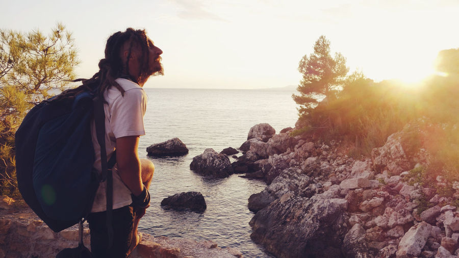 Backpack Beach Beauty In Nature Climbing Coast Dreadlocks Happiness Long Hair Man Nature One Person Relaxation Rock Rock Climbing Rocks Sea Sky Summer Sunlight Sunset Sunset_collection Travel Traveling Vacations Young Adult