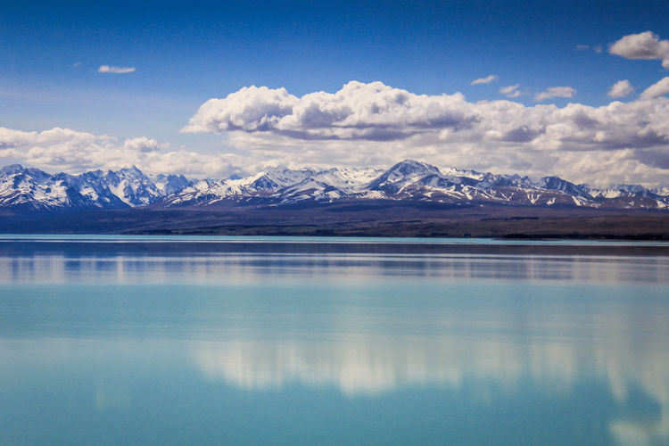 Reflection of snowcapped mountains in lake against cloudy sky