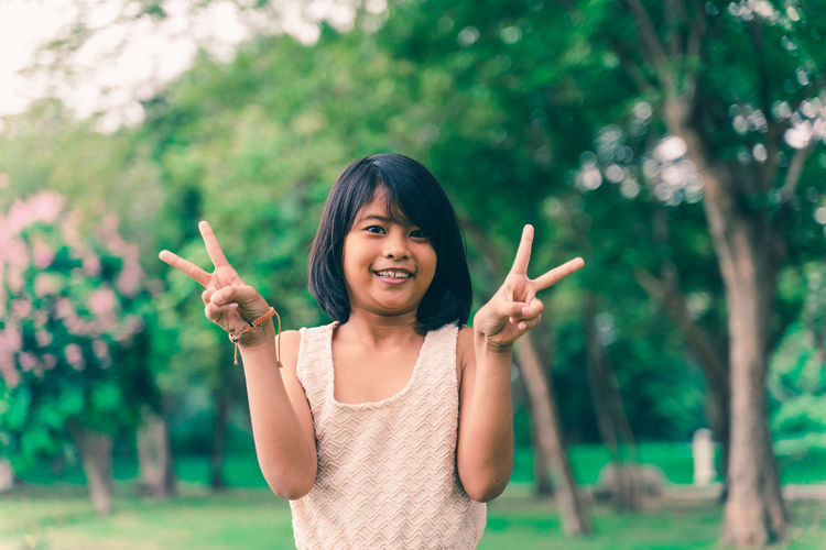 Portrait of smiling girl gesturing peace sign while standing at park