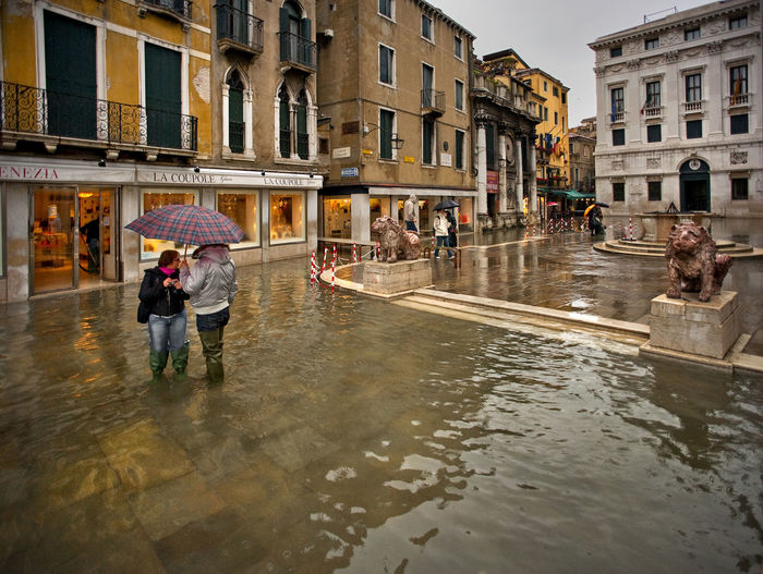 Italy, Venice, Grand Canal, Piazza San Marco, the flood, the Cathedral of San Marco Architecture Boat Building Exterior Canal City Life Culture Destination Incidental People Men Nautical Vessel Outdoors Real People Reflection Transportation Urban Walking Water Waterfront Weekend Activities Women
