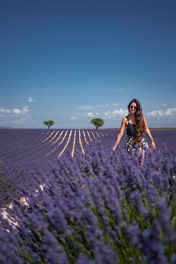 Woman standing on field by purple flowering plants against sky