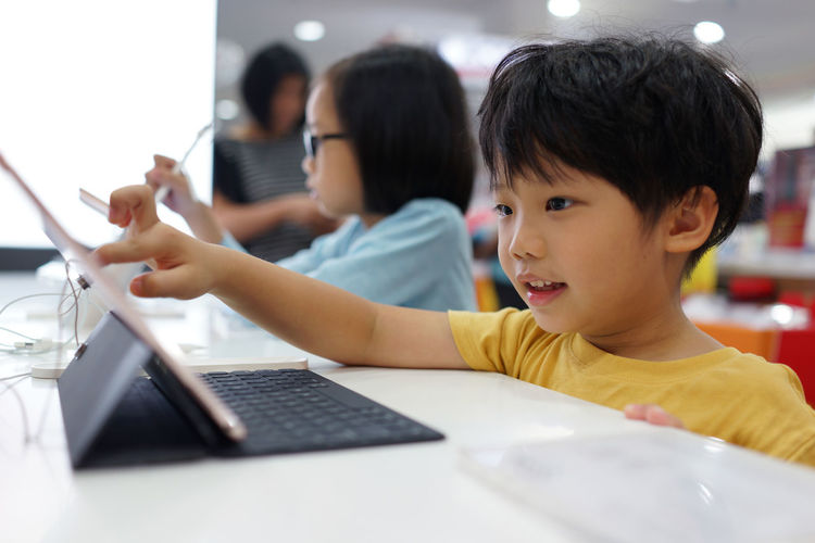 Cute siblings using laptop at table