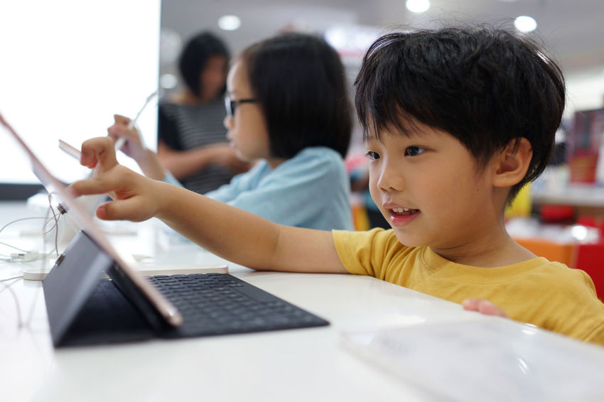 Portraits of little boy and girl using tablet in the store Electronic Devices Tablet Boys Child Childhood Communication Computer Connection Education Girls Group Of People Indoors  Innocence Laptop Real People Retail Store Shop Table Technology Using Laptop Wireless Technology