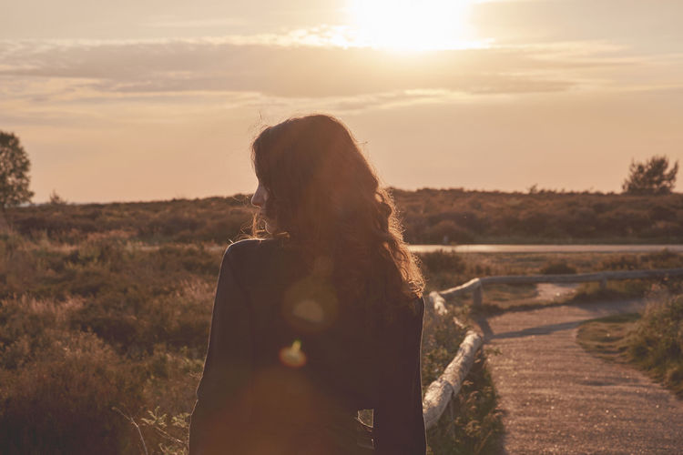 Adult Beauty In Nature Contemplation Hair Hairstyle Land Leisure Activity Lens Flare Lifestyles Long Hair Nature One Person Outdoors Real People Rear View Sky Standing Sun Sunlight Sunset Waist Up Women Young Adult