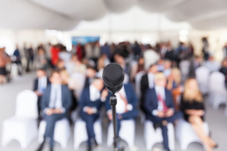 Close-up of microphone with business people sitting in background during seminar