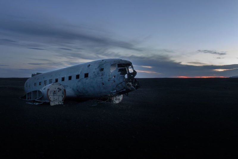 Abandoned airplane on land against sky during sunset