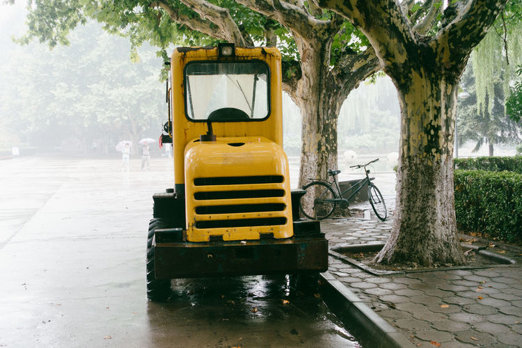 Yellow vehicle on wet road by trees in city