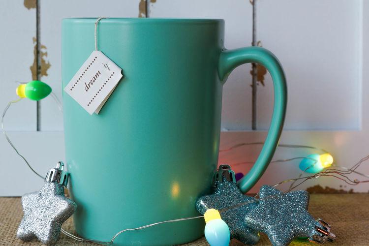 Close-Up Of Coffee Mug With Star Shapes And Christmas Lights On Table