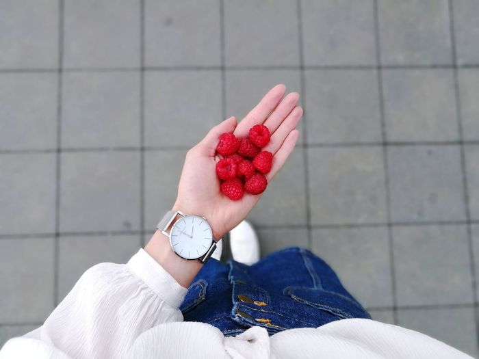 Low section of woman holding raspberries