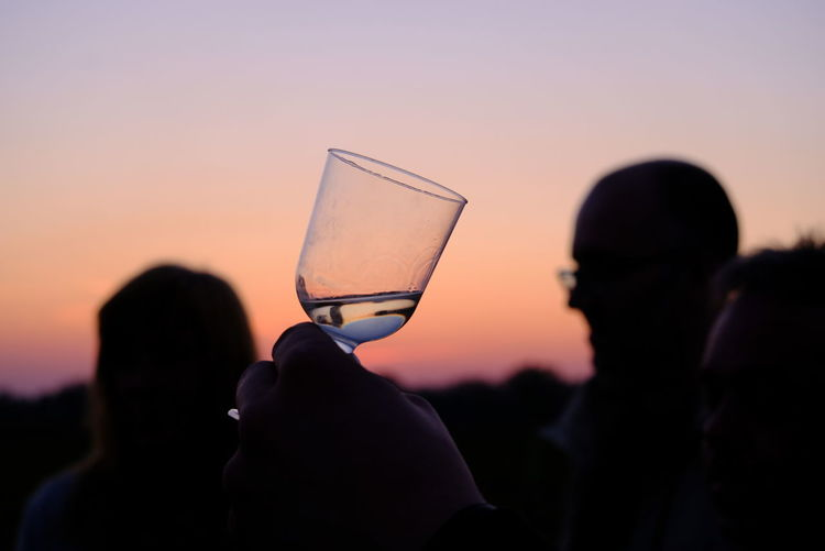 Close-up of silhouette man drinking glass against sunset sky