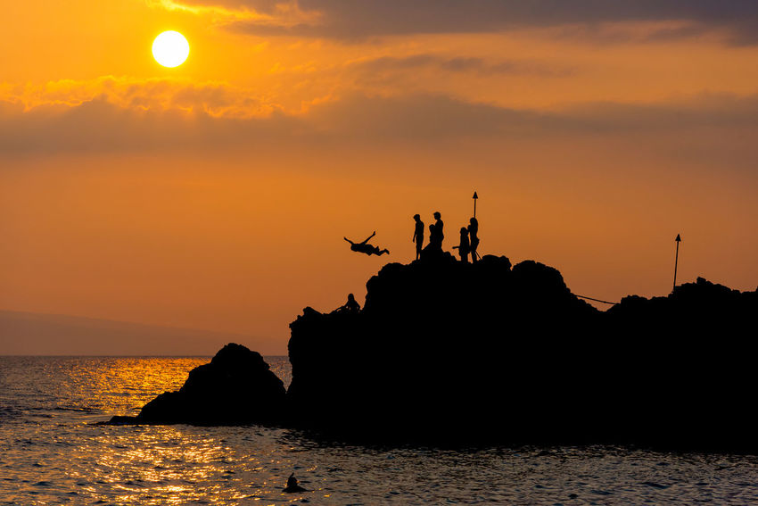 Silhouette of Diver Leaping off Rock and into the Water around Sunset in Maui, Hawaii Beauty In Nature Competition Horizon Over Water Mammal Men Nature Orange Color Outdoors People Real People Rock - Object Scenics Sea Silhouette Sky Sport Sunset Sunset #sun #clouds #skylovers #sky #nature #beautifulinnature #naturalbeauty #photography #landscape Tranquil Scene Tranquility Water