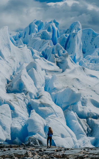 Woman standing against the prep perito moreno glacier