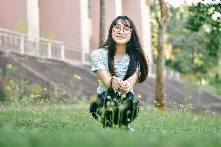 Portrait of cheerful young woman crouching on grass against building at park