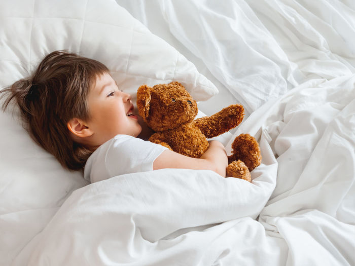 Cute baby girl lying on bed