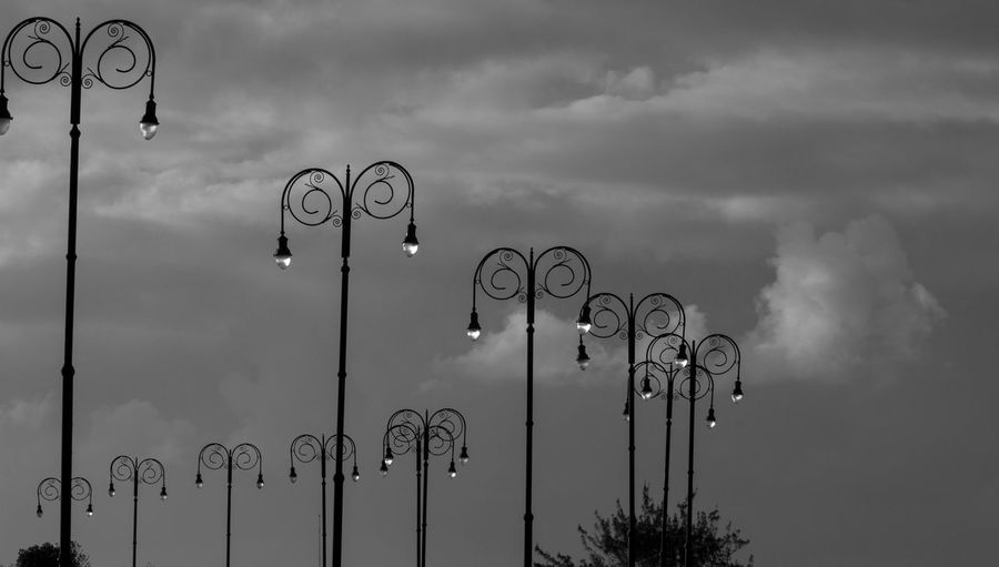 Low angle view of street lights in row against cloudy sky during dusk