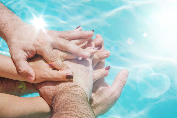High angle view of hands stacking over swimming pool