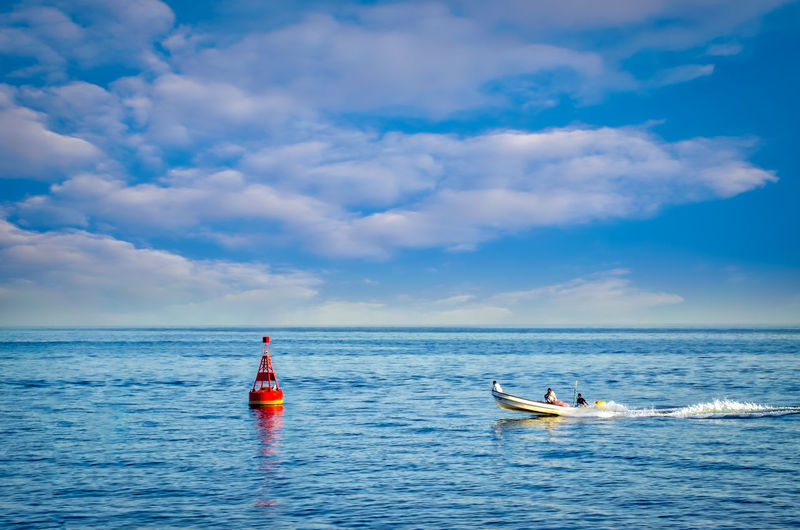Men Riding Boat On Scenic Sea Against Sky