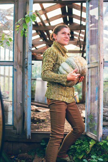 Young woman holding a big ripe pumpkin collected from garden. thanksgiving and halloween preparation