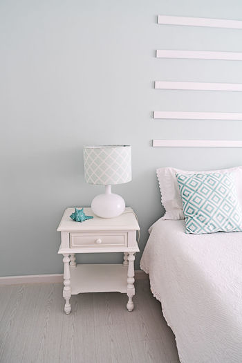 White table and chairs on bed against wall at home
