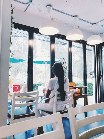 Adult Cafe Casual Clothing Chair Day Food And Drink Indoors  Leisure Activity Lifestyles People Real People Restaurant Seat Sitting Table Three Quarter Length Waiting Window Women Young Adult