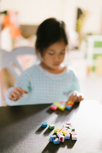 Beads Child Childhood Concentration Day Domestic Life Education Human Body Part Human Hand Indoors  Looking Down One Person People Playing Toy Block Wooden Toys
