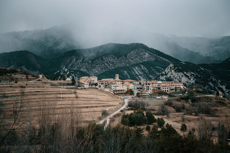 Panoramic view of village against mountain range