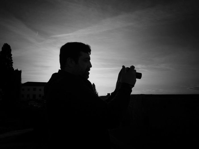 Man photographing against sky