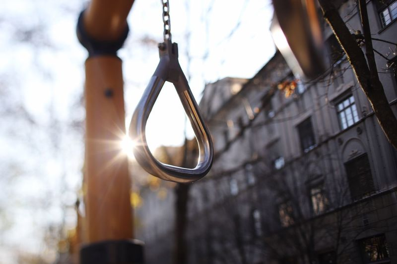 Lift yourself up. Calisthenics Healthy Lifestyle Fitness Sport Equipment Sport Movement Hanging Focus On Foreground Low Angle View Outdoors Day No People Sunlight Nature Metal Close-up Architecture Tree Lens Flare Lighting Equipment Swing Sky Illuminated Built Structure