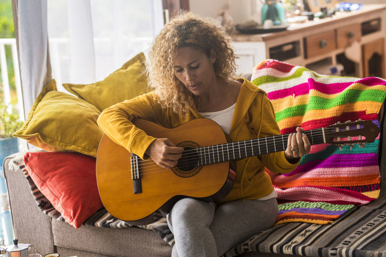Mature woman playing guitar sitting on sofa at home