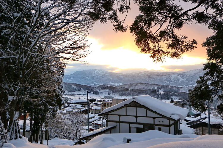 Sunset over the Japanese mountain village Beauty In Nature Cold Temperature Frozen House Mountain Nature No People Outdoors Residential Building Scenics Sky Snow Sunset Tranquil Scene Tree Vacations Winter Winter In Japan