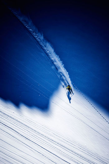 Aerial view of man skiing on snowcapped mountain