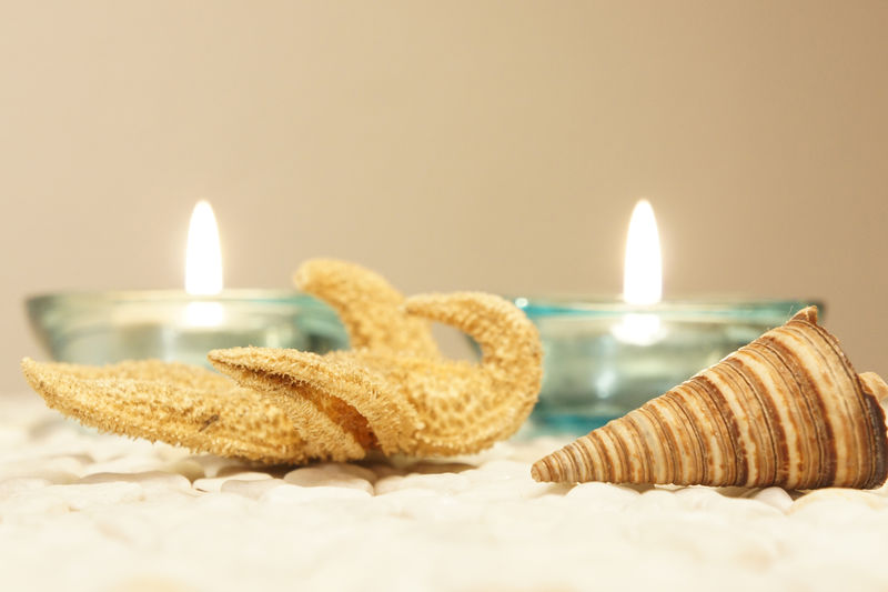 Close-Up Of Starfish With Seashell And Lit Tea Light Candles On Table