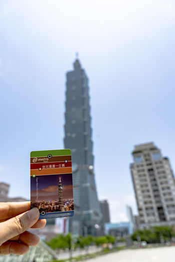 Taiwan 1 day pass MRT ticket in hand with blurry Taipei 101 building background 1 Day Pass MRT Ticket Taiwan MRT Ticket One Day Trip 101 Tower 101 Taipei Sunny Day