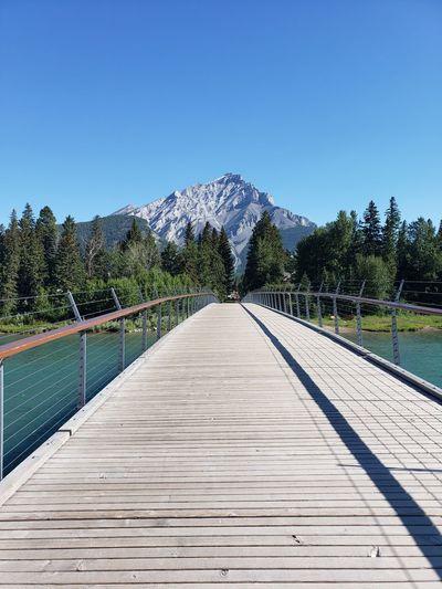 View of footbridge against clear blue sky