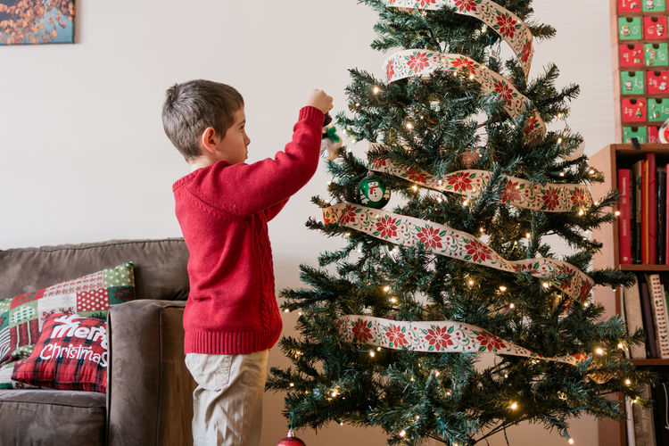 Boy with christmas tree at home