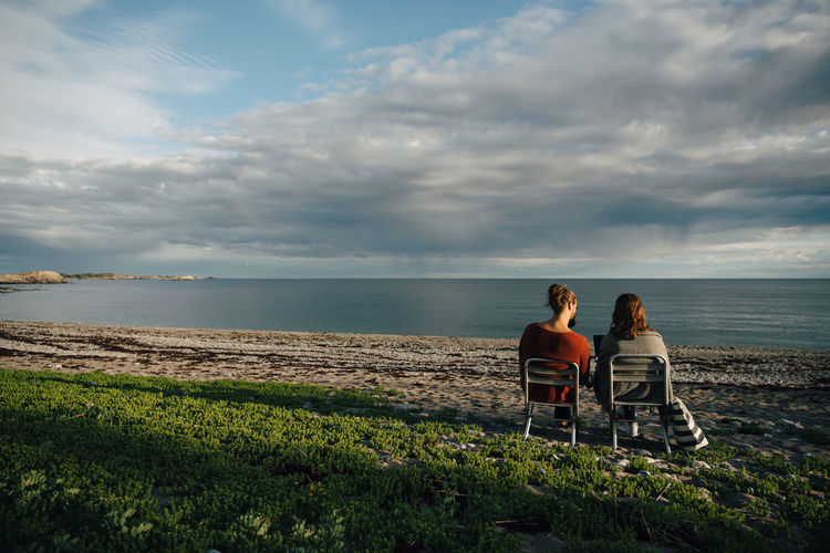 Friends sitting on shore at beach against sky